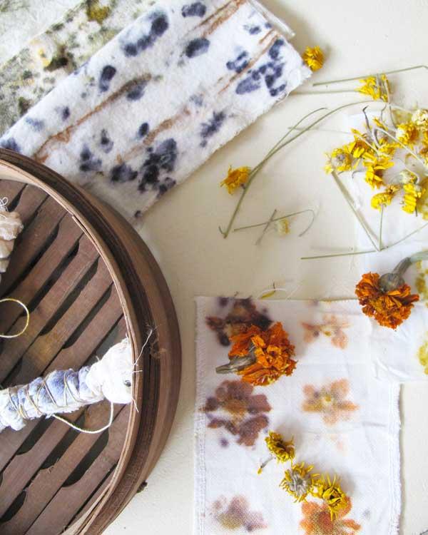 Mit Blueten gefärbte Stoffe, mit gelben, rostroten, violetten und olivgrünen Mustern auf hellem Hintergund, mit trockener Färberkamille und Tagetes.