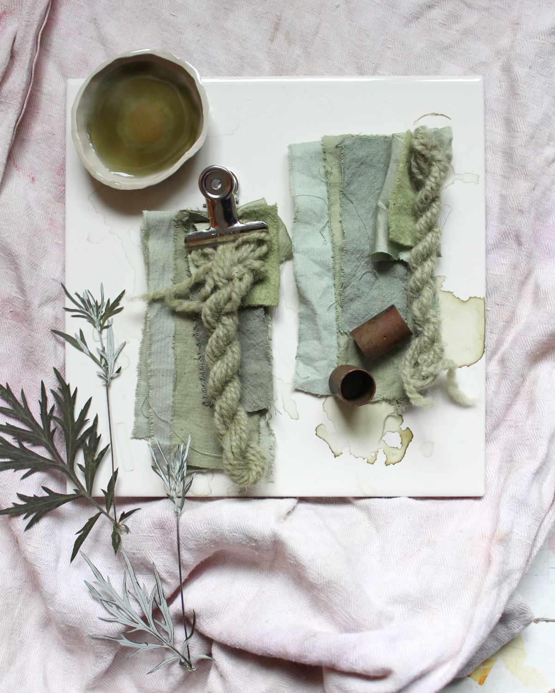 Stoffe und Wolle gefaerbt in hellen Grüntönen, mit einem getrockneten Beifuß-Blatt